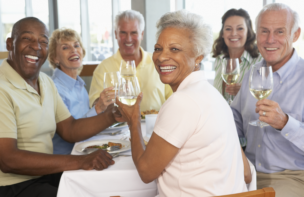 three senior couples toasting at lunch