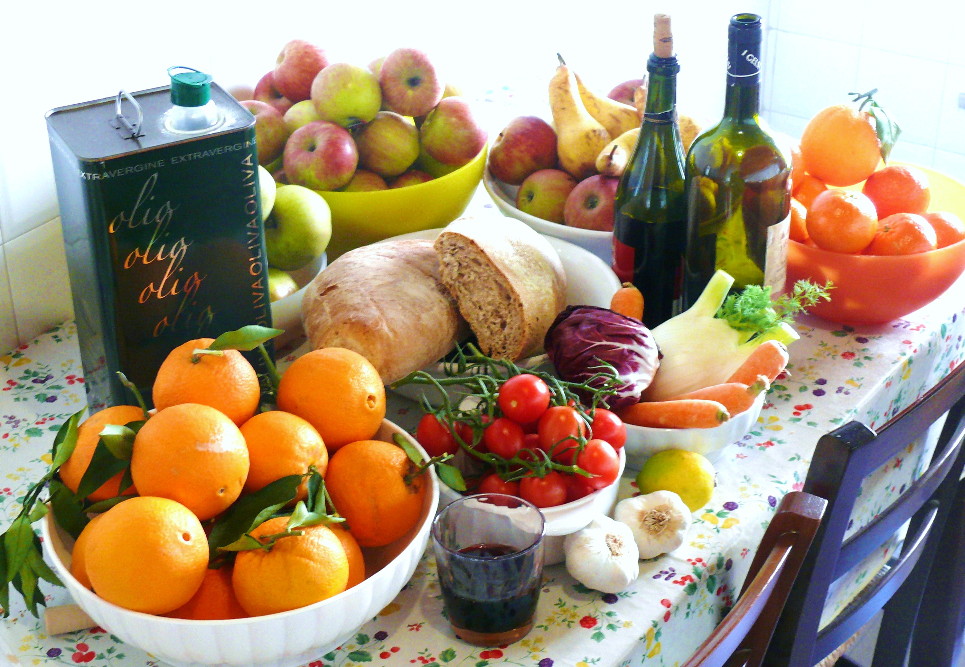 a table set with fruit, vegetables, olive oil and wine