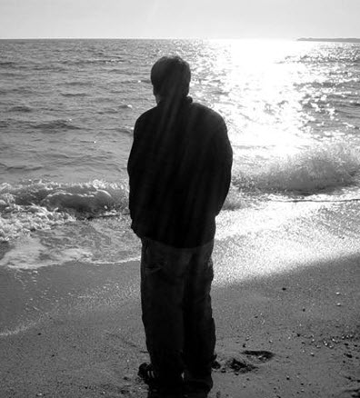 senior standing at the edge of the sea