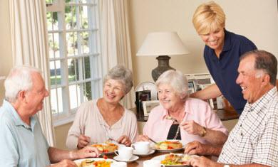five seniors enjoying a meal together