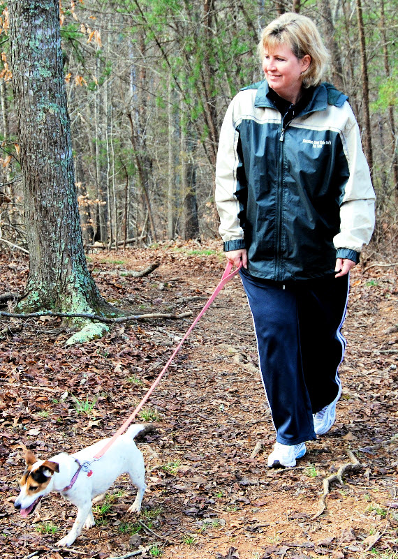 a person walking a dog in the forest